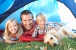 Young father poses with children in tent